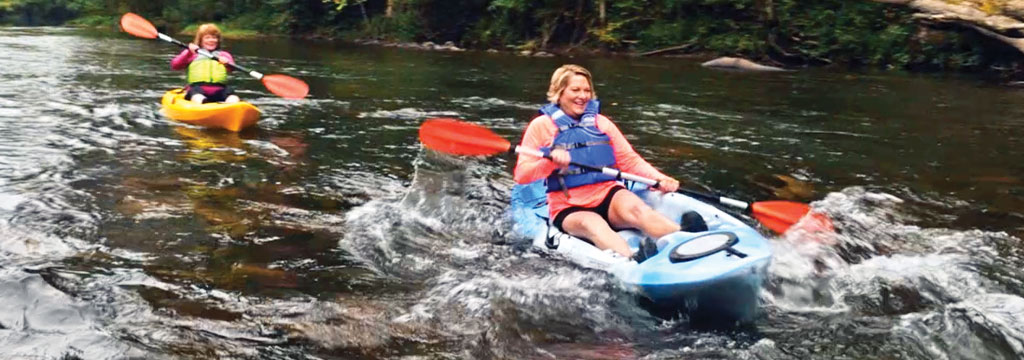 ladies kayaking through rapids